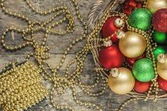 Το κόκκινο σφαιρών Χριστουγέννων, χρυσός, πράσινος, χάντρες βρίσκεται σε ένα ξύλινο καλάθι τ Στοκ Εικόνα