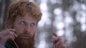 Το κόκκινο τα ακουστικά -αυτιών ενθέτων ατόμων στο χειμερινό δάσος απόθεμα βίντεο