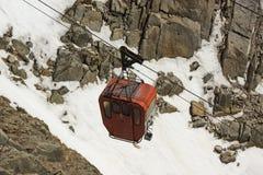 Το κόκκινο τελεφερίκ στον τρόπο στα δύσκολα βουνά Στοκ εικόνα με δικαίωμα ελεύθερης χρήσης