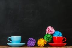 Το κόκκινο φλυτζάνι καφέ χύνει τις ζαρωμένες σφαίρες εγγράφου χρώματος Στοκ Φωτογραφία
