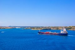 Το κόκκινο φορτηγό πλοίο του /blue πηγαίνει κατά μήκος της ακτής Menorca, Ισπανία Στοκ Φωτογραφίες