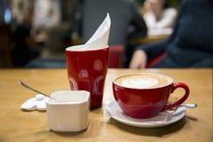 Το κόκκινο φλιτζάνι του καφέ με τον αφρό, το ανοικτές κύπελλο ζάχαρης και η πετσέτα επιζητούν Στοκ Εικόνες