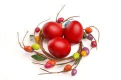 Το κόκκινο χέρι έβαψε τα αυγά Πάσχας με τη διακόσμηση φωλιών αυγών Πάσχας κύκλων γύρω από τους. Στοκ εικόνα με δικαίωμα ελεύθερης χρήσης