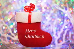 Το κόκκινο δώρο αισθάνθηκε την μπότα με τη Χαρούμενα Χριστούγεννα λέξεων σε ένα χρωματισμένο β στοκ φωτογραφία με δικαίωμα ελεύθερης χρήσης