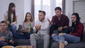 Το κόμμα Σαββατοκύριακου στον καναπέ, φίλοι νεολαίας ομάδας πίνει την μπύρα και τρώει την πίτσα προσέχοντας τον κινηματογράφο στη φιλμ μικρού μήκους
