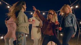 Το κόμμα χορού, αστεία νεολαία απολαμβάνει τις διακοπές στην ωκεάνια ακτή στο φωτισμό των γιρλαντών τη νύχτα απόθεμα βίντεο