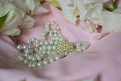 Το κόσμημα στα άσπρα μαργαριτάρια και τα λουλούδια είναι σε ένα ελαφρύ χρωματισμένο ύφασμα στοκ φωτογραφία με δικαίωμα ελεύθερης χρήσης