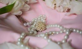Το κόσμημα στα άσπρα μαργαριτάρια και τα λουλούδια είναι σε ένα ελαφρύ χρωματισμένο ύφασμα στοκ φωτογραφίες με δικαίωμα ελεύθερης χρήσης