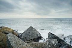 Το κύμα χτυπά το βράχο στην παραλία Στοκ Φωτογραφία
