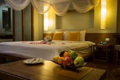 Το κύπελλο των εξωτικών φρούτων και του θολωμένου υποβάθρου με τους κύκνους πετσετών, κόκκινο αυξήθηκε πέταλα στο κρεβάτι, διακόσ στοκ φωτογραφίες