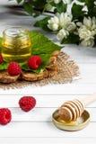 Το κύπελλο με το μέλι, τα μούρα και τα φύλλα του σμέουρου σε μια ξύλινη στάση Κουτάλι με το μέλι, λουλούδια της Jasmine Στοκ Εικόνες