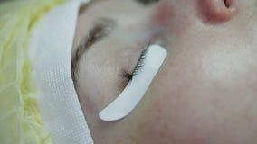 Το κύριος-cosmetician ενισχύει eyelashes στο όμορφο κορίτσι Κινηματογράφηση σε πρώτο πλάνο φιλμ μικρού μήκους