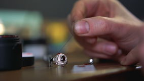 Το κύριο χέρι ` s εφαρμόζει το κόκκινο σμάλτο στο ασημένιο δαχτυλίδι με ένα ειδικό εργαλείο φιλμ μικρού μήκους