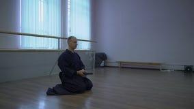 Το κύριο Kendo κάθεται στο πάτωμα και βρίσκεται ενώπιον του ξίφος Katana ` s στη θήκη φιλμ μικρού μήκους