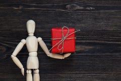 Το κλασικό ξύλινο ομοίωμα κρατά το κόκκινο κιβώτιο δώρων Στοκ Εικόνα