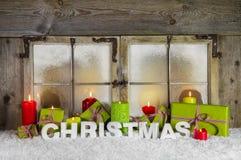 Το κλασσικό παράθυρο Χριστουγέννων με τα κεριά και παρουσιάζει για τα Χριστούγεννα Στοκ Φωτογραφία