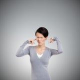 Το κλείσιμο των αυτιών με τη γυναίκα δάχτυλων παρεκκλίνει τα μάτια της στοκ φωτογραφία