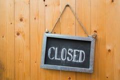 Το κλειστό σημάδι κρεμά στην ξύλινη πόρτα Στοκ φωτογραφία με δικαίωμα ελεύθερης χρήσης