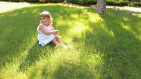 Το λίγο γλυκό κορίτσι κάθεται στη χλόη στο πάρκο, πορτρέτο απόθεμα βίντεο