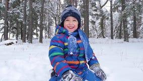 Το λίγο ευτυχές αγόρι κάθεται στο χιόνι σε ένα χειμερινό πάρκο ή ένα δάσος και γελά Αναψυχή και παιχνίδια στη φύση Παιδιά ` s φιλμ μικρού μήκους