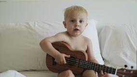 Το λίγο ξανθό αγόρι εξετάζει τη κάμερα και παίζει ukulele φιλμ μικρού μήκους