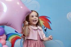 Το λίγο χαμογελώντας κορίτσι σε ένα ρόδινο σακάκι και μια φούστα σκονών είναι hol Στοκ φωτογραφίες με δικαίωμα ελεύθερης χρήσης