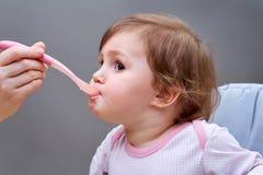 Το λίγο χαριτωμένο κορίτσι ταΐζεται με ένα κουτάλι του πουρέ φρούτων στο γκρίζο υπόβαθρο Στοκ Φωτογραφία