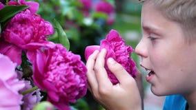 Το λίγο χαριτωμένο μωρό απολαμβάνει ήπια τη μυρωδιά των λουλουδιών Το παιδί παίρνει ένα λουλούδι και εισπνέει το άρωμά του ανθίζο απόθεμα βίντεο