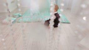Το λίγο 1χρονο αγόρι παίζει στο πάτωμα του σπιτιού κοντά στη σκηνή παιχνιδιών φιλμ μικρού μήκους