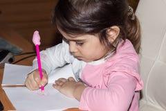 Το λίγο όμορφο κορίτσι επισύρει την προσοχή σε ένα φύλλο του εγγράφου πορτρέτο κινηματογραφήσεων σε πρώτο πλάνο ενός 3χρονου κορι στοκ εικόνες