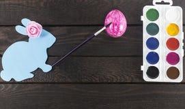 Το λαγουδάκι καρτών με το πινέλο σε το χέρι ` s και ρόδινος αυξήθηκε σε το κεφάλι ` s, χρωματίζοντας το αυγό στο ροζ Στοκ εικόνα με δικαίωμα ελεύθερης χρήσης