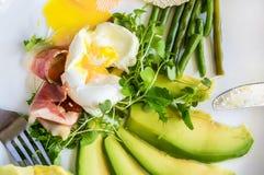 Το λαθραίο αυγό στο σπίτι με τα πράσινες φασόλια σαλάτας μωρών και τις φέτες του αβοκάντο σε ένα άσπρο πιάτο Στοκ Εικόνα