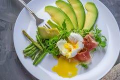 Το λαθραίο αυγό στο σπίτι με τα πράσινες φασόλια σαλάτας μωρών και τις φέτες του αβοκάντο σε ένα άσπρο πιάτο Στοκ φωτογραφία με δικαίωμα ελεύθερης χρήσης