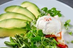 Το λαθραίο αυγό στο σπίτι με τα πράσινες φασόλια σαλάτας μωρών και τις φέτες του αβοκάντο σε ένα άσπρο πιάτο Στοκ Φωτογραφίες