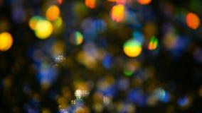 Το λαμπύρισμα Defocused πολύχρωμο ακτινοβολεί κομφετί, μαύρο υπόβαθρο Ελαφριά σημεία bokeh διακοπών αφηρημένα εορταστικά απόθεμα βίντεο