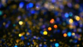 Το λαμπύρισμα Defocused πολύχρωμο ακτινοβολεί κομφετί, μαύρο υπόβαθρο Ελαφριά σημεία bokeh διακοπών αφηρημένα εορταστικά φιλμ μικρού μήκους