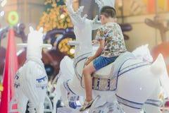 Το λατρευτό ασιατικό αγόρι παιδάκι που οδηγά σε έναν εύθυμο πηγαίνει γύρω από carouse στοκ εικόνα