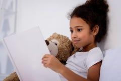 το λατρευτό βιβλίο και το αγκάλιασμα ανάγνωσης παιδιών αφροαμερικάνων teddy αντέχουν Στοκ φωτογραφία με δικαίωμα ελεύθερης χρήσης