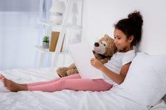 το λατρευτό βιβλίο και το αγκάλιασμα ανάγνωσης παιδιών αφροαμερικάνων teddy αντέχουν Στοκ Εικόνες