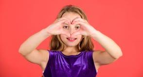 Το λατρευτό κορίτσι παιδιών με το μακρυμάλλες πρόσωπο χαμόγελου σας παρουσιάζει χειρονομία καρδιών σε Γιορτάστε την ημέρα βαλεντί στοκ εικόνα