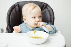 Το λατρευτό μωρό κάθεται στην υψηλή καρέκλα και τρώει τη σούπα κρέμας Στοκ Φωτογραφία