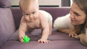 Το λατρευτό μωρό σέρνεται στο ιώδες κρεβάτι Γυμνό παιδί στις πάνες που ροκανίζουν το παιχνίδι φιλμ μικρού μήκους