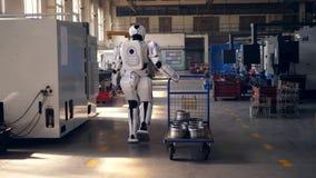 Το λειτουργώντας ρομπότ τραβά ένα κάρρο μετάλλων, περπατώντας σε μια δυνατότητα απόθεμα βίντεο