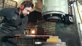 Το λειωμένο μέταλλο υποβάλλεται σε επεξεργασία υπό πίεση στα χέρια ενός σιδηρουργού, ευρεία γωνία απόθεμα βίντεο