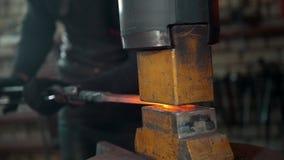 Το λειωμένο μέταλλο υποβάλλεται σε επεξεργασία υπό πίεση στα χέρια ενός σιδηρουργού απόθεμα βίντεο
