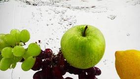 Το λεμόνι, το μήλο και τα σταφύλια που εμπίπτουν στο νερό με τις φυσαλίδες Βίντεο σε σε αργή κίνηση Τα φρούτα απομόνωσαν ένα άσπρ απόθεμα βίντεο