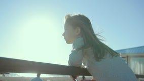 Το λεπτός-κοίταγμα κορίτσι στέκεται και κλίνει στα κιγκλιδώματα σε μια ακροθαλασσιά στην slo-Mo απόθεμα βίντεο