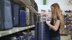 Το λεπτό κορίτσι παίρνει τη μεγάλη βαλίτσα από ένα ράφι της υπεραγοράς για την εξέταση απόθεμα βίντεο
