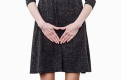 Το λεπτό κορίτσι σε ένα σκοτεινό φόρεμα δοκιμάζει την ταλαιπωρία στη μήτρα, πόνος, χέρια μεταξύ των ποδιών της Η ακράτεια, πρέπει στοκ εικόνες με δικαίωμα ελεύθερης χρήσης