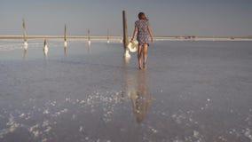 Το λεπτό προκλητικό κορίτσι που απολαμβάνει ένα ηλιοβασίλεμα, περπατά ήπια στο νερό μιας αλατισμένης λίμνης φιλμ μικρού μήκους